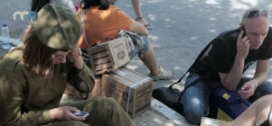 Israelis make phone calls from a Tel Aviv sidewalk after waiting in line for government-issued gas masks.