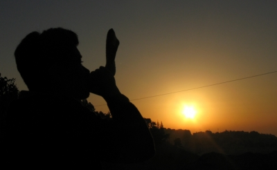 Someone blows a shofar as the sunrises over Jerusalem.