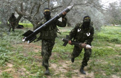 Masked Palestinian militants from Islamic Jihad run with homemade rockets to put in place before later firing them into Israel on the outskirts of Gaza City. (Photo by Amir Farshad Ebrahimi/Flickr).